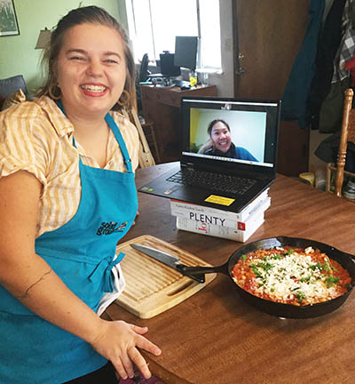 Two women, one in an apron next to a laptop and a pan of food, one on the laptop screen