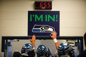 "Seahawks tap the ""I'm In"" sign on their way to the field"