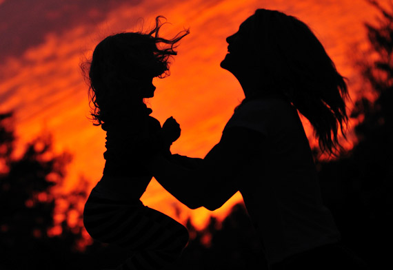 Silhouette of a mother lifting her young daughter joyfully with a bright orange sky behind them