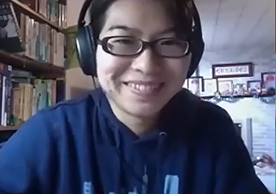 Asian woman with glasses and a blue shirt, wearing headphones, smiles during a Zoom video