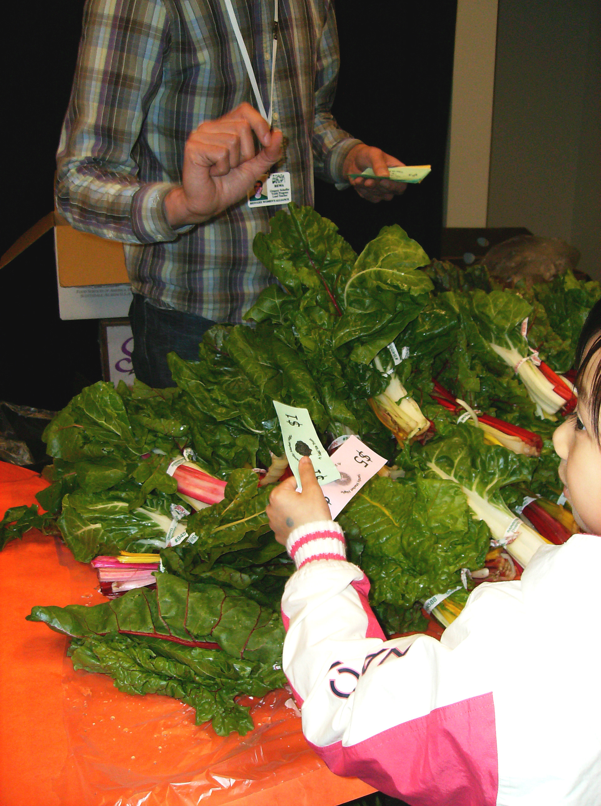 "At an Apple Corps ""Market Night,"" a student uses ""dollars"" to purchase rainbow chard."
