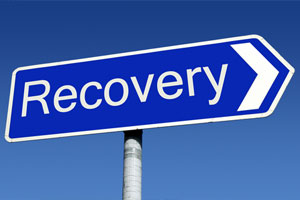 """Blue road sign in the shape of an arrow that says """"Recovery"""" in white letters"""