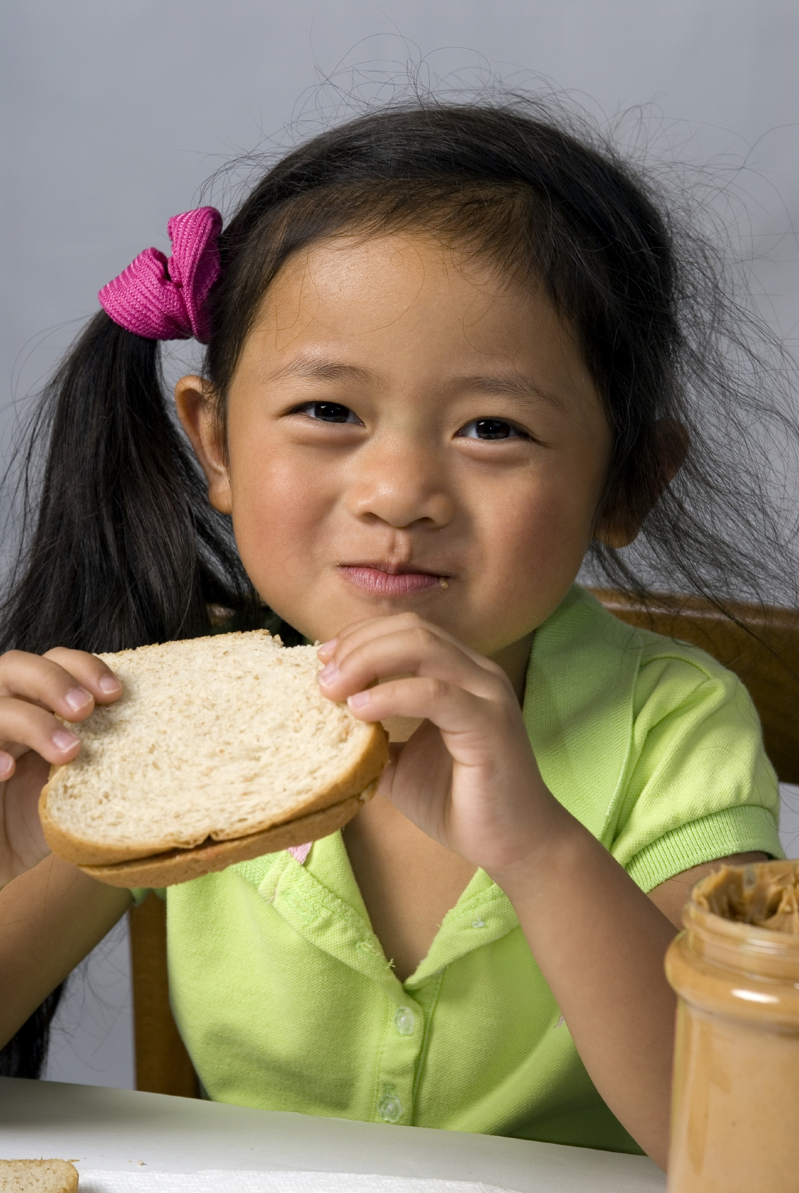 A young child makes a peanut butter and Jelly sandwich