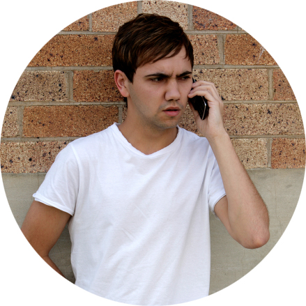 Guy on Cellphone by Brick Wall