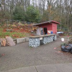 A before shot of the Seattle Community Farm work tables and toolshed. The pink markers on the ground indicate the locations of the support posts for the canopy.