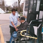 SGT driver Roland Remolana raises a passenger and his wheelchair onto a Metro ACCESS van.