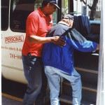 Ninus Hopkins helps an elderly passenger board the ACCESS van.