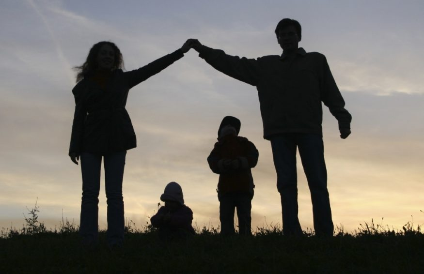 silhouette of a family with two adults forming a roof over the heads of two children at sunset
