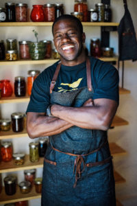 Acclaimed Seattle Chef Edouardo Jordan surrounded by jars of pickled foods