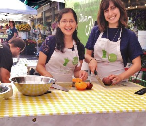 Sandra & Addie prepare food in the sun at a cooking demo at Pike Place Market.