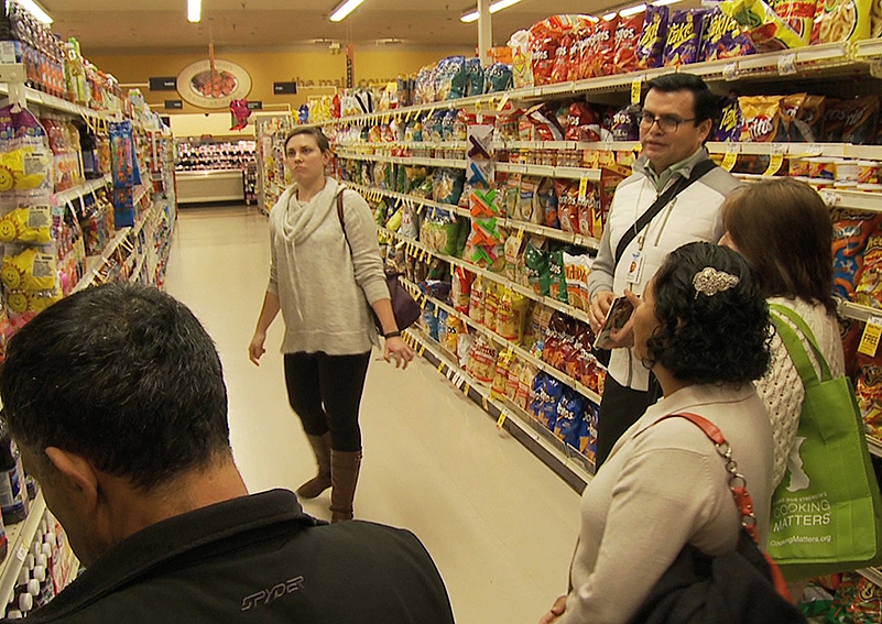 Cooking Matters volunteer Edgar Lopez gives a Spanish-language grocery store tour