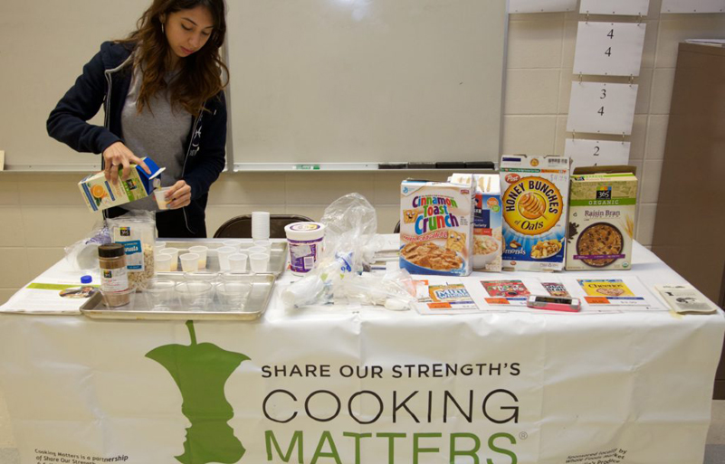 AmeriCorps member Michelle Huete prepares for a pop-up Cooking Matters at the Store tour.