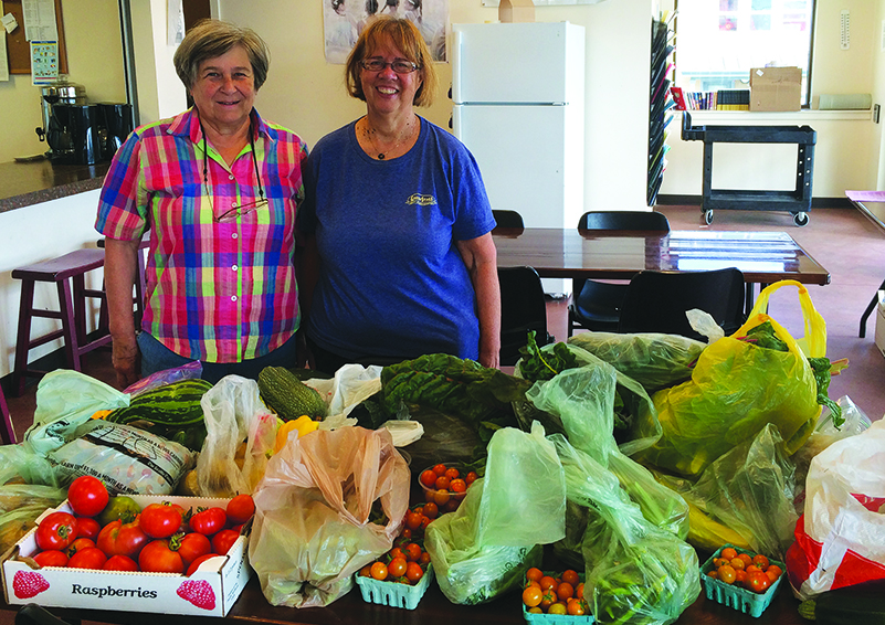 MCG gardeners Marty DeLong (l) and Kathy Dugaw (r) drop off a smorgasbord of veggies for residents of Solid Ground's Sand Point Housing campus (photo by Christina Shimizu).