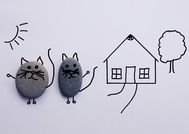 Line drawing of house with two cats made of rocks