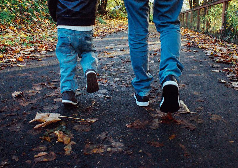 Father & son walk on a leafy path
