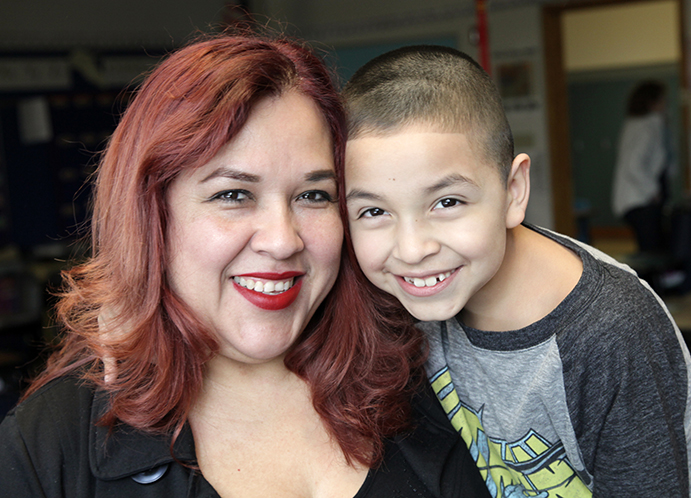 "Maricela & Jonathan in his 2nd grade general ed classroom: ""Every day I repeat with him, 'I am smart, kind and handsome,' and he likes that part, of course! He is getting more aware of his potential, because when he's reading he says, 'I know how to read! You want me to read a book for you?'"" (photo by Bellen Drake)"