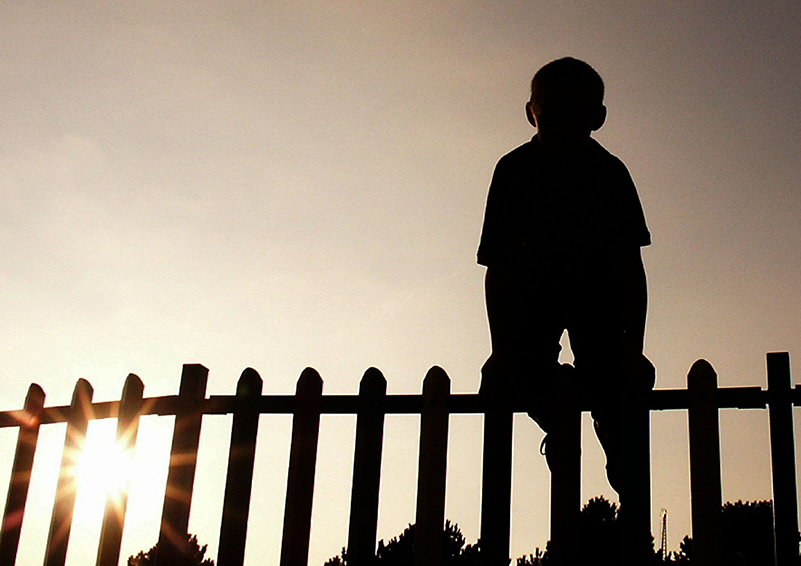 silhouette of boy climbing a fence