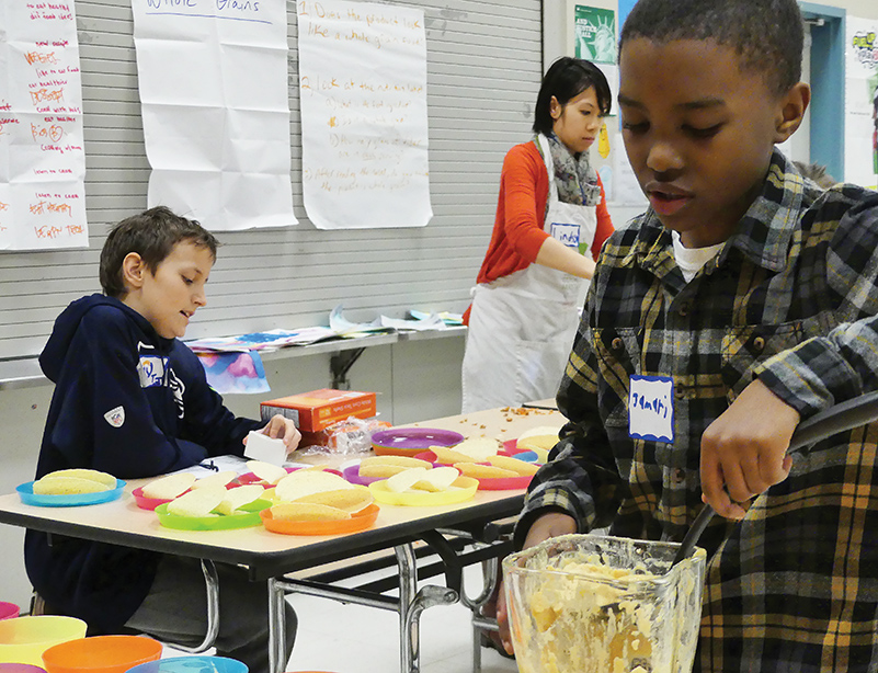 Jamari serves his carefully spiced hummus for his classmates (photos by Liz Reed Hawk).