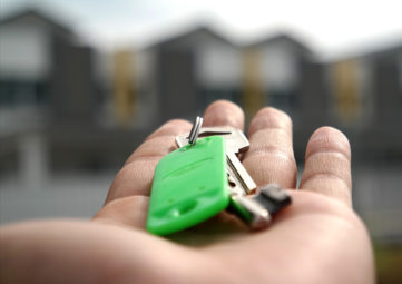 Keys in hand with housing in the background