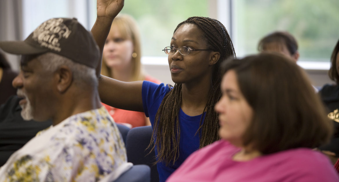 Black woman raises her hand to ask a question during a workshop