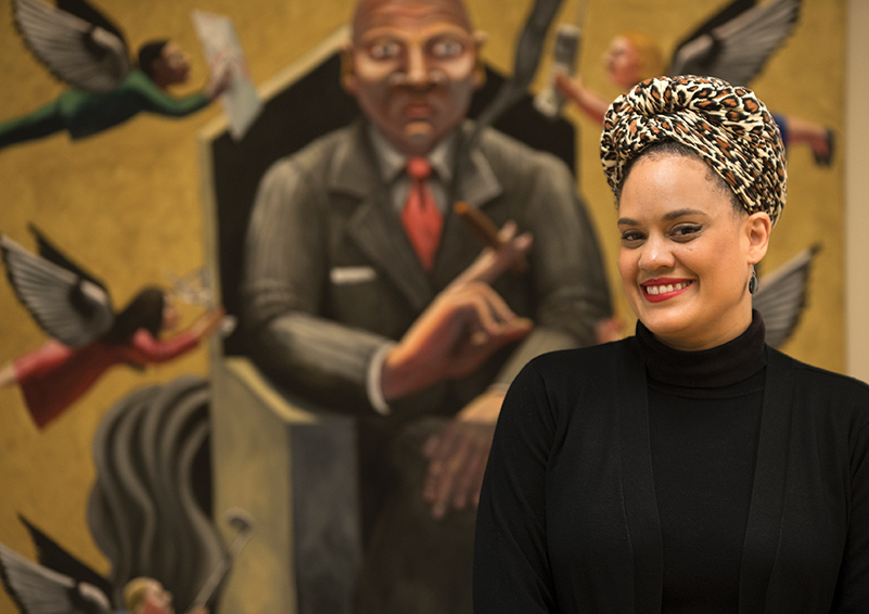 Lhorna Murray – artist, activist, community organizer & Sand Point Housing resident – poses in front of 'Office Deity' by Pacific NW artist John Feodorov (photo by Chris Villiers   Writing, Photography & Strategic Communications).