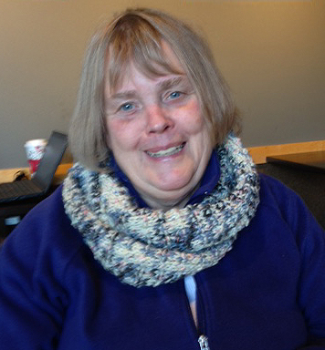 Linda sporting the colorful scarf she knitted (photo by Peter Langmaid)