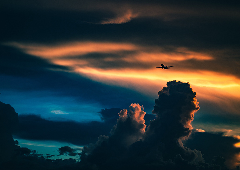Airplane flying through a dramatic cloudy, sunset sky over mountains and an aquamarine body of water