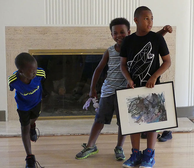 Left to right: Young artists Dang, Karamie & Tyrece; Karamie throws his arm around his brother's shoulder as Tyrece comments on what art means to him.