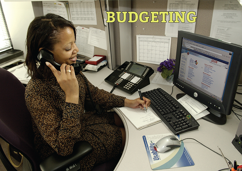 Budgeting: Woman on the phone at her computer takes notes on a notepad