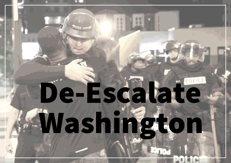 Police and protester hug under banner that says De-Escalate Washington