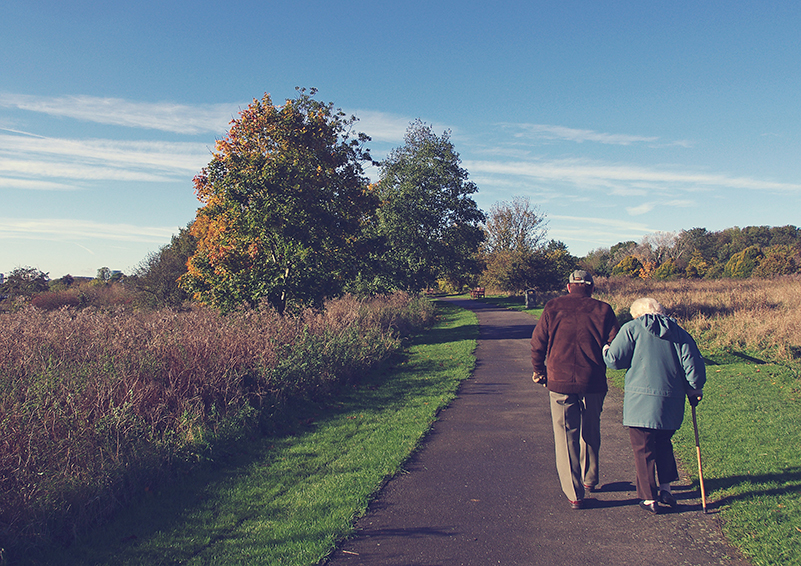 Elderly couple walk down a path