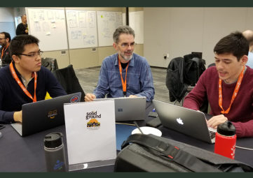 GiveCamp's Xuan Wang & Maxwell Rediker consult with Solid Ground Data Systems Developer, Joseph Boland, to finalize an emergency messaging system for Sand Point Housing residents.