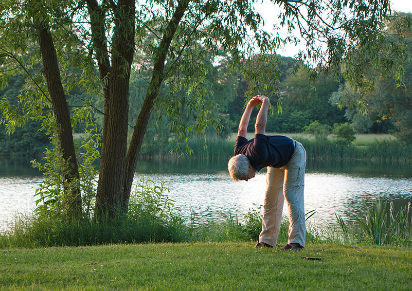 Senior stretching by lake