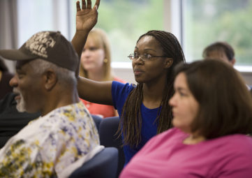 Woman raises hand in community meeting
