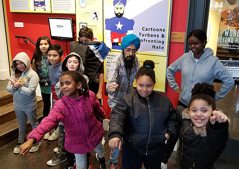 Cartoonist & activist Vishavjit Singh poses with Sand Point Housing resident youth by an exhibit of his work at the Wing Luke Museum.