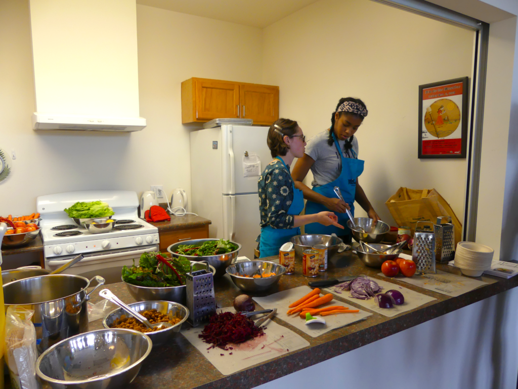 Two youth educators prep food.