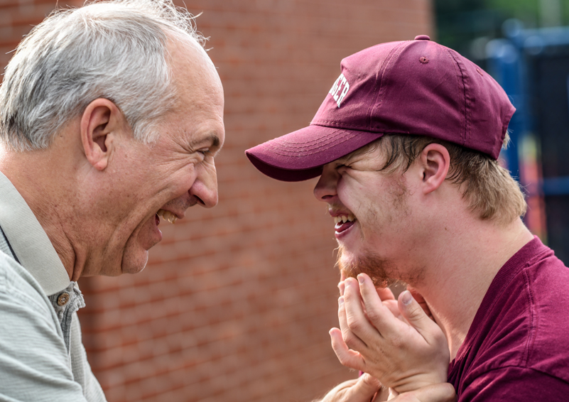 A senior man laughs with a developmentally delayed younger man