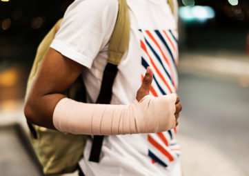 Young person with sprained wrist gives a thumbs up.