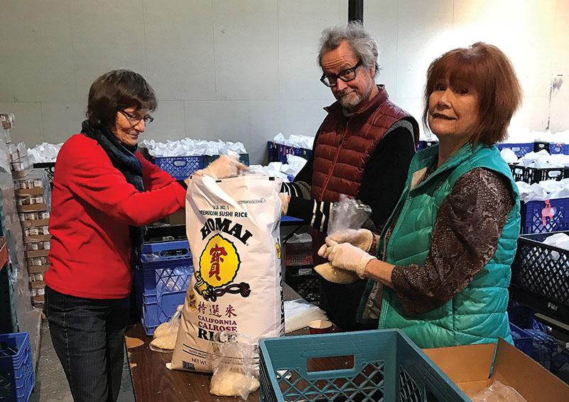 RSVP volunteers Sarah Parkhurst, David Thornbrugh, and Charla Sullivan bagging rice for the Backpack Brigade
