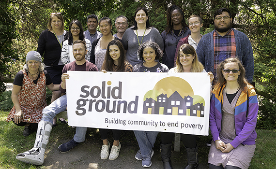 Group photo of Solid Ground staff members holding a Solid Ground banner, June 2019 (photo by Chris Villiers)