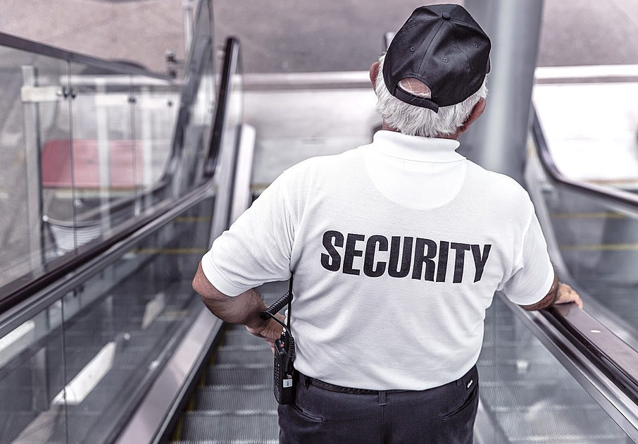 A white-haired security guard with black cap takes the escalator