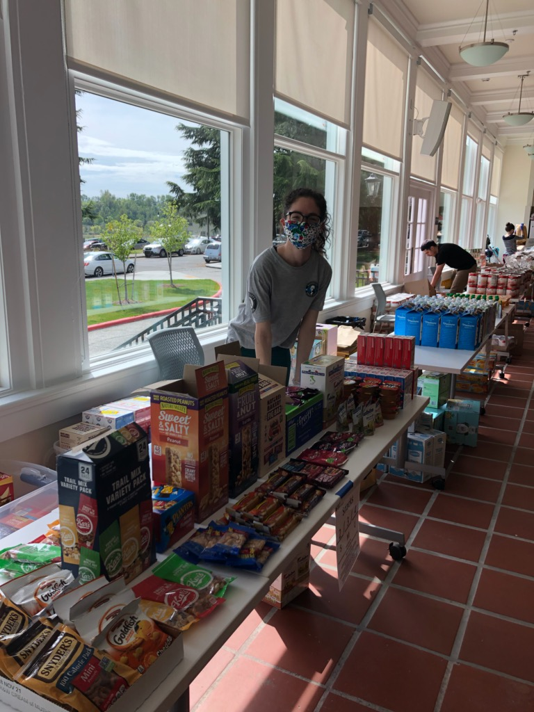 Woman wearing a face mask and glasses behind a food pantry table filled with food products