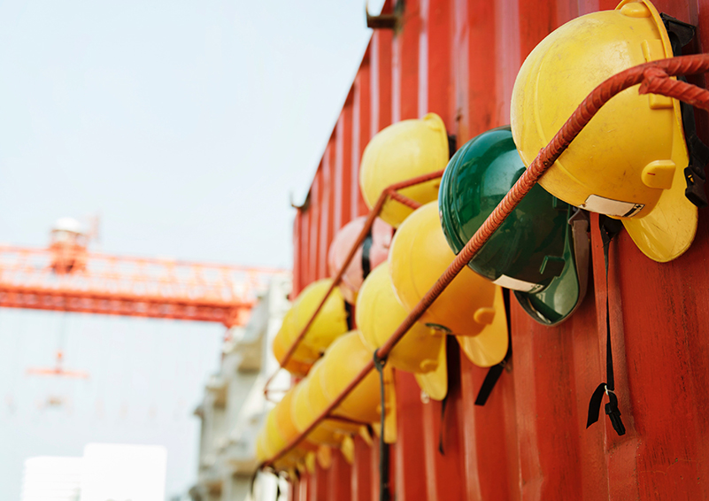 Hard hats hanging on the side of a storage container, with a tower crane in the background