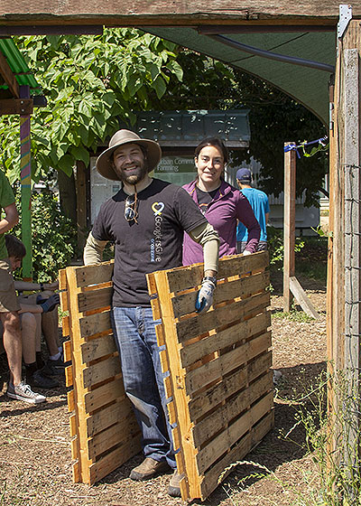 Two Google employees haul pallets at a Giving Garden at Marra Farm work party, summer 2018