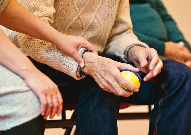 A women gently holding the wrist of an elderly man holding a ball