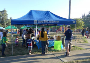 Families stand at the entrance to the back-to-school tabling area.