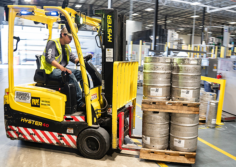 Man in hard hat drives a forklift in a container crate factory