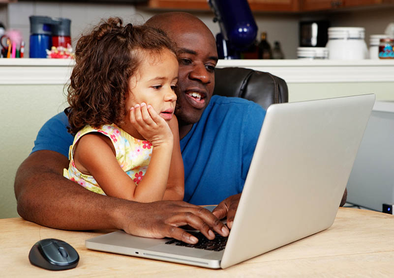 A father and his small daughter look at a laptop together at their kitchen table