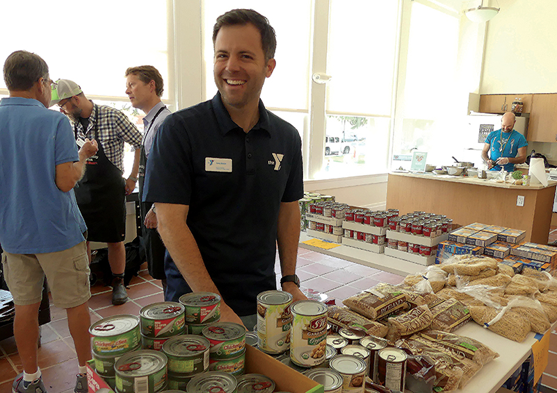 Andy Sharpe, Executive Director of the University Family YMCA, smiles in front of a canned goods displayon opening day of the Magnuson Park Community Food Pantry