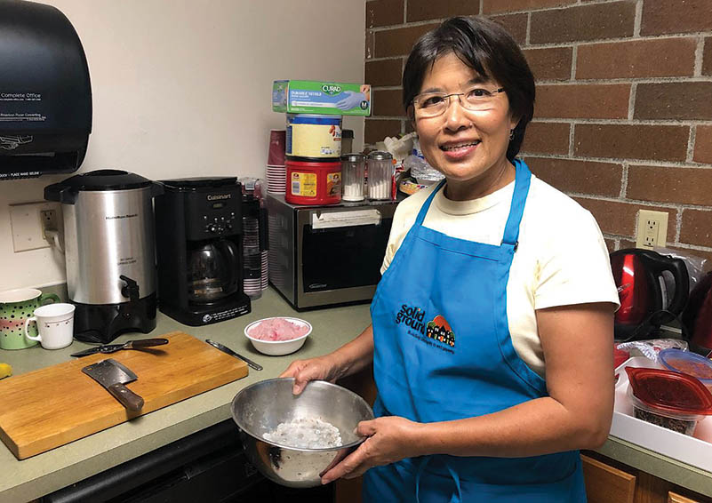A cooking class volunteer in a blue apron holds a bowl of flour